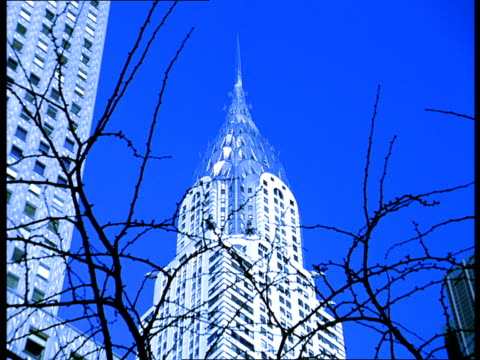 the spire on the chrysler building looks like glass against a blue sky. - spire stock videos & royalty-free footage