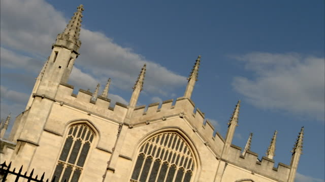 the spires of the university of oxford contrast against a blue sky. - turmspitze stock-videos und b-roll-filmmaterial