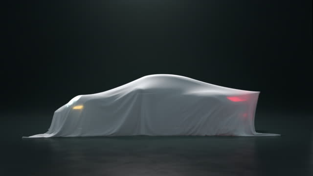 the sport car is covered with a white cloth on a black background. the fabric falls from the vehicle but under it is nothing. - prototype stock videos & royalty-free footage