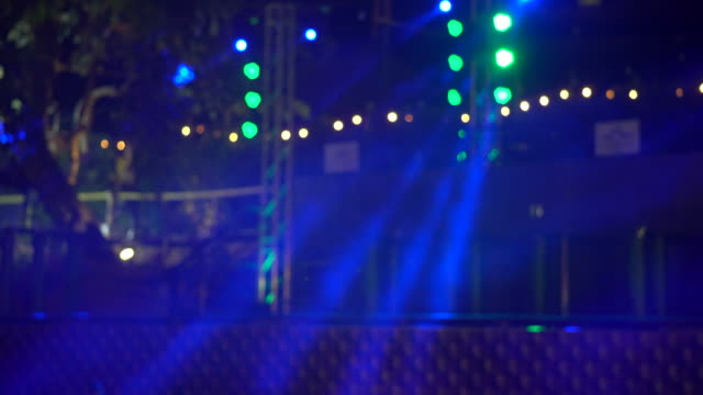 Die Scheinwerfer durch den Rauch auf der Bühne.