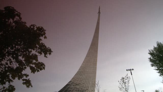 the sputnik monument rises skyward in a moscow park. available in hd. - sputnik video stock e b–roll