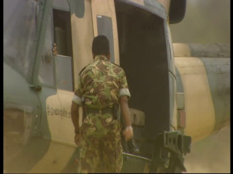 the sri lankan air force delivers the first supplies of rice and sugar to a village cut off in the indian ocean tsunami and following monsoon rains - 2004 stock-videos und b-roll-filmmaterial