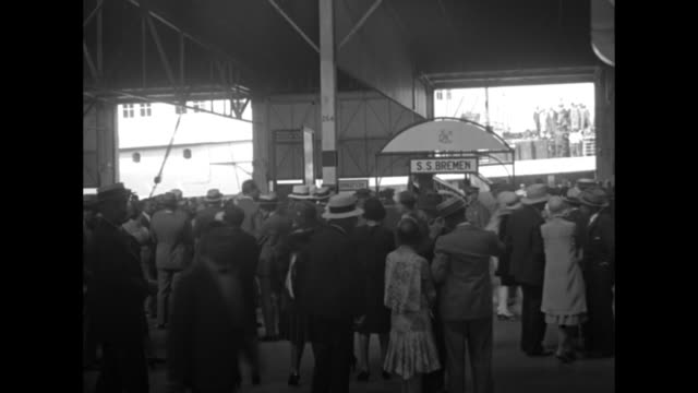 the ss bremen accompanied with tugboats comes into dock with crowds of people at railings / vs passengers mill around customs area with the ship... - passagier wasserfahrzeug stock-videos und b-roll-filmmaterial