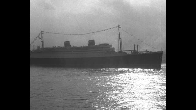 the ss manhattan slowly moves into new york harbor / a crowd on a dock with the ship approaching sunlight reflected on the water with the uss akron... - passing a note stock videos & royalty-free footage