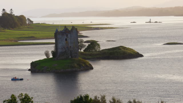 the stalker castle on island with golden light in the middle of the sea in scotland. - castle island stock videos & royalty-free footage