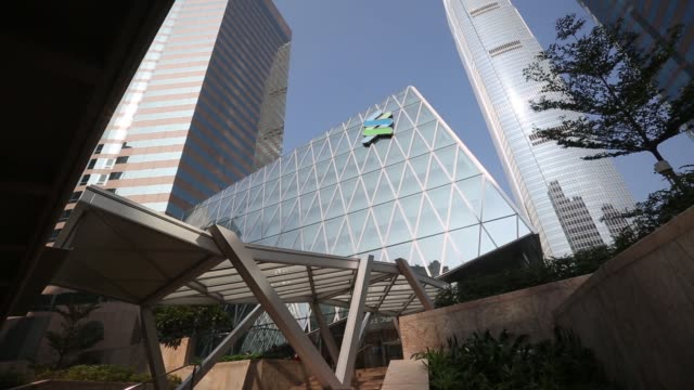 the standard chartered plc logo is displayed outside the standard chartered bank building as it stands next to hsbc holdings plc headquarters in the... - plc stock videos & royalty-free footage