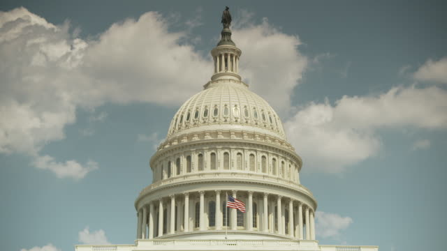 the stars and stripes flies in front of the dome of the united states capitol building on a sunny day, washington, d.c., usa. - house of representatives stock videos & royalty-free footage