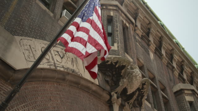 the stars and stripes hangs from a flagpole outside the 69th regiment armory on lexington avenue, manhattan, site of the 1913 armory show, new york city, usa. - military recruit stock videos & royalty-free footage