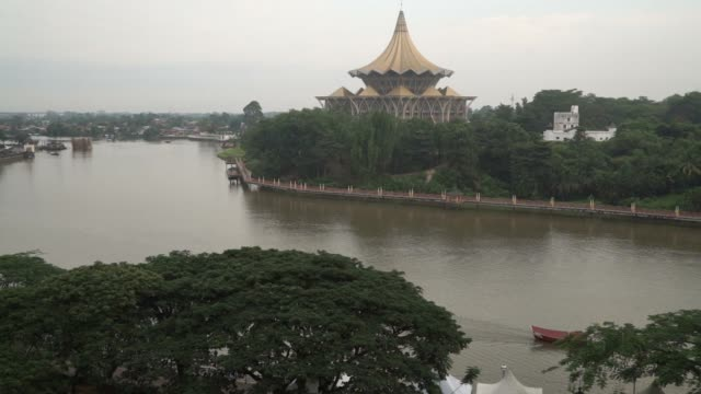 the state legislative assembly complex, center, stands near the sarawak river in kuching, sarawak, malaysia, on wednesday, april 13 buildings stand... - サラワク州点の映像素材/bロール