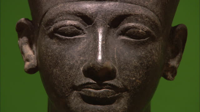 The statue of a pharaoh stands against a green wall.