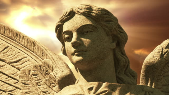 The statue of an Angel on time lapse golden clouds (Loop).