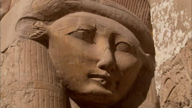 the statue of an egyptian woman's face overlooks the temple grounds at deir el-bahari in egypt. available in hd. - hatschepsut tempel stock-videos und b-roll-filmmaterial