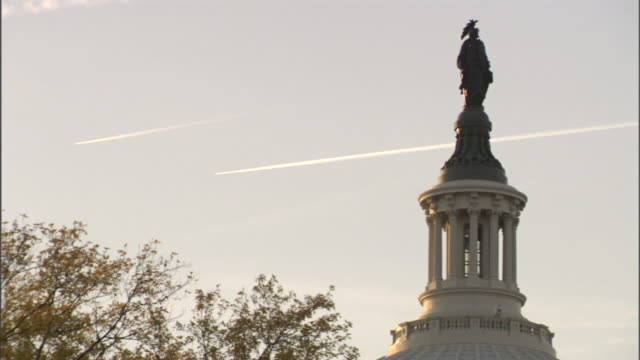 the statue of freedom adorns the top of the capitol building in washington, d.c. - politics icon stock videos & royalty-free footage