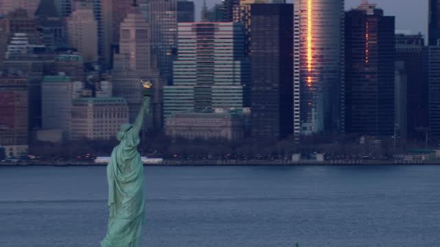 vídeos de stock, filmes e b-roll de the statue of liberty and the island of manhattan in new york city at twilight. - estátua