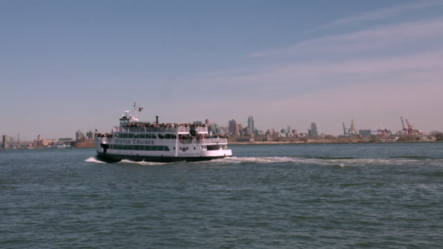 ts the statue of liberty ferry sailing through new york harbor / new york, united states - fähre stock-videos und b-roll-filmmaterial