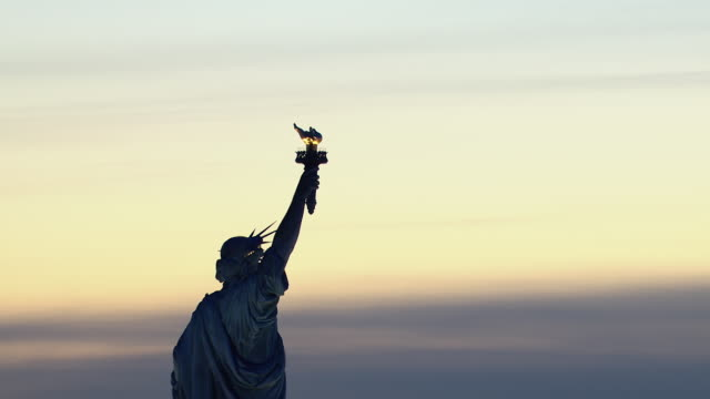 the statue of liberty greets the dawn with her torch in new york city. - statue of liberty new york city stock videos & royalty-free footage