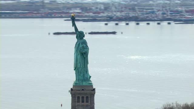 vídeos de stock, filmes e b-roll de the statue of liberty looks out over the new york harbor in new york city, new york, usa. - estátua