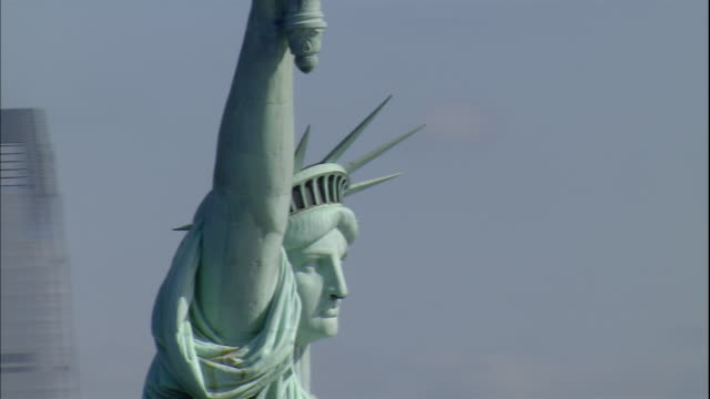 the statue of liberty looks out over the new york harbor. - freiheitsstatue stock-videos und b-roll-filmmaterial