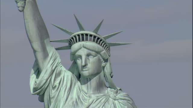 the statue of liberty looks out over the new york harbor. - statue of liberty new york city stock videos & royalty-free footage