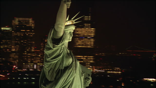 the statue of liberty overlooks the twinkling lights of manhattan in new york city, new york. - freiheitsstatue stock-videos und b-roll-filmmaterial