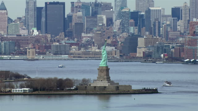 the statue of liberty stands in front of a backdrop of skyscrapers in lower manhattan. - female likeness stock videos & royalty-free footage