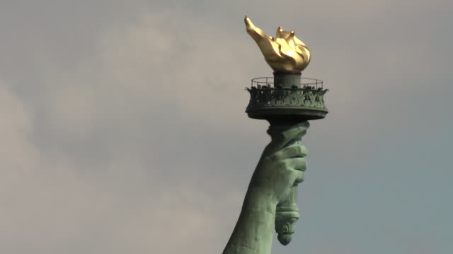 CU of the Statue of Liberty's hand and touch during the daytime.