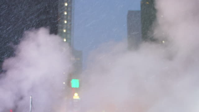 vídeos de stock, filmes e b-roll de the steam rises and drifts over the avenue among the midtown manhattan buildings in the snow night, which glow and illuminated from digital billboard around the times square in midtown manhattan new york city ny usa on jan. 18 2020. - times square manhattan