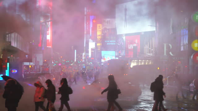 the steam rises and drifts over the avenue among the midtown manhattan buildings in the snow night, which glow and illuminated from digital billboard around the times square in midtown manhattan new york city ny usa on jan. 18 2020. - vapour trail stock videos & royalty-free footage