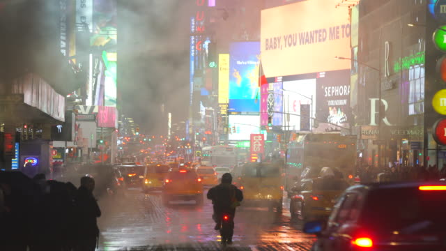 the steam rises and drifts over the avenue among the midtown manhattan buildings in the snow night, which glow and illuminated from digital billboard around the times square in midtown manhattan new york city ny usa on jan. 18 2020. - yellow taxi stock videos & royalty-free footage