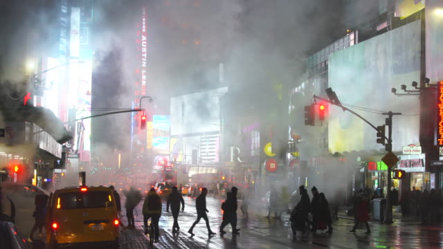 the steam rises and drifts over the avenue among the midtown manhattan buildings in the snow night, which glow and illuminated from digital billboard around the times square in midtown manhattan new york city ny usa on jan. 18 2020. - chimney stock videos & royalty-free footage