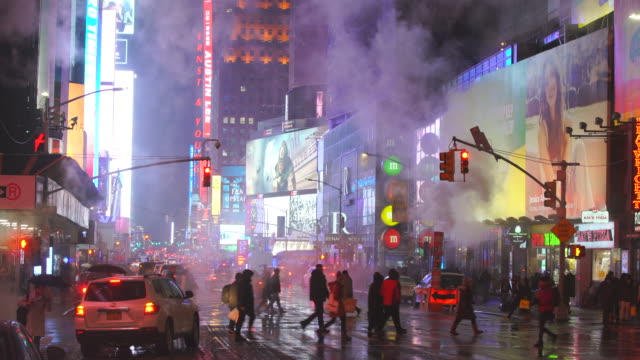 the steam rises and drifts over the avenue among the midtown manhattan buildings in the snow night, which glow and illuminated from digital billboard around the times square in midtown manhattan new york city ny usa on jan. 18 2020. - projection screen stock videos & royalty-free footage