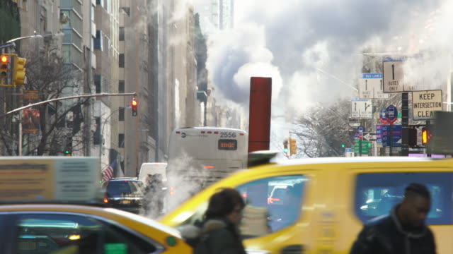 the steam rises and drifts over the midtown manhattan traffic and people cross on the 5th avenue at new york city ny usa on jan. 09 2020. - yellow taxi stock videos & royalty-free footage