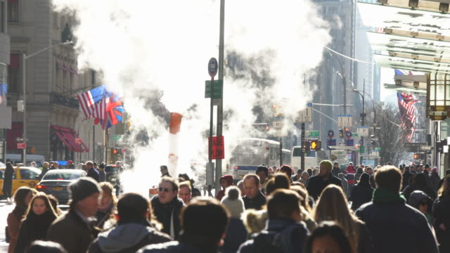 the steam rises and drifts over the midtown manhattan traffic and people cross on the 5th avenue at new york city ny usa on jan. 09 2020. - viale video stock e b–roll