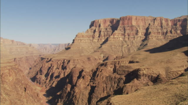 the steep walls of the grand canyon tower over the colorado river. - river colorado stock videos & royalty-free footage