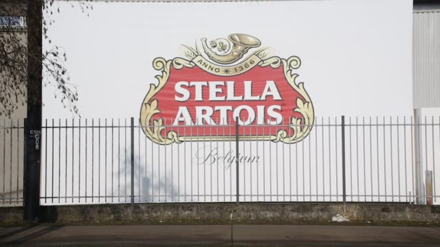 the stella artois lager beer logo sits on the exterior of the anheuserbusch inbev nv brewery in leuven belgium on saturday march 3 photographer dario... - anheuser busch inbev stock videos and b-roll footage