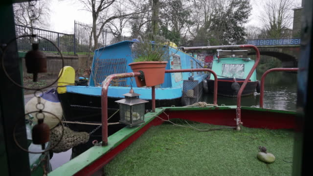 the stern and decking of a narrow boat, double moored in victoria park, london in winter - moored stock videos & royalty-free footage