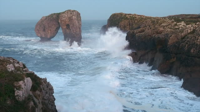 the stone arch called the castro de las gaviotas on the east coast of asturias whipped during a storm by the wind and the strong waves of the cantabrian sea. llanes, asturias. - eroded stock videos & royalty-free footage
