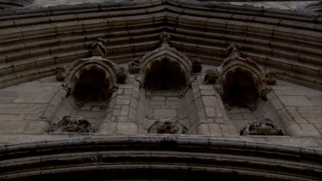 the stone awning of st edmundsbury cathedral overhangs three recessed arches. available in hd. - awning stock videos & royalty-free footage