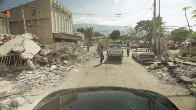 the streets of portauprince with building debris on the edge of the street after the haiti earthquake of january 2010 - ポルトープランス点の映像素材/bロール
