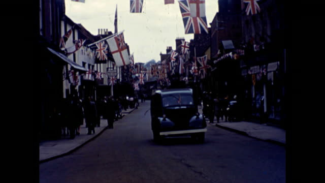 the streets of the small town of godalming are lined with union jacks and bunting as residents celebrate ve day victory in europe day 1945 as germany... - ve day stock-videos und b-roll-filmmaterial