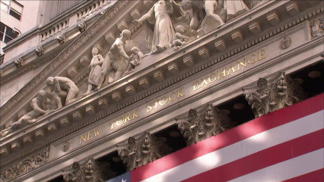 the stripes of an american flag hang below the ornately carved pediment of the new york stock exchange on wall street. - ペディメント点の映像素材/bロール