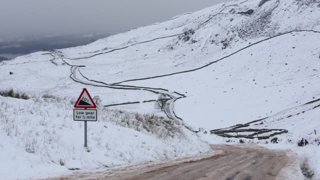 the struggle to the summit of kirkstone pass from ambleside, closed by snow, lake district, uk. - road closed sign stock videos & royalty-free footage