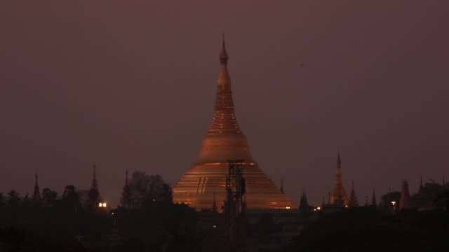 The stupa of Shwedagon Pagoda surrounded by smaller stupas stand stand illuminated after sunset in Yangon Myanmar on Tuesday March 7 2017