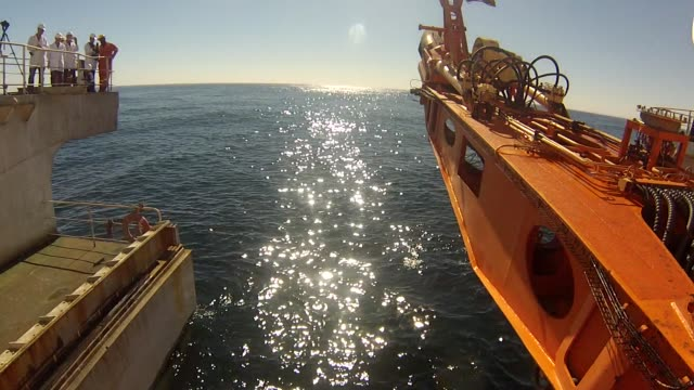 stockvideo's en b-roll-footage met the suction arm of the crawler tractor used to suck sediment from the seabed drops into the sea from the mafuta diamond mining vessel operated by... - oceaanbodem