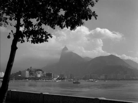 the sugar loaf mountain towers above the city of rio de janeiro 1961 - 景勝地点の映像素材/bロール
