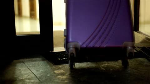 vídeos de stock, filmes e b-roll de a mala de mão de até o hotel. - mala de rodinhas