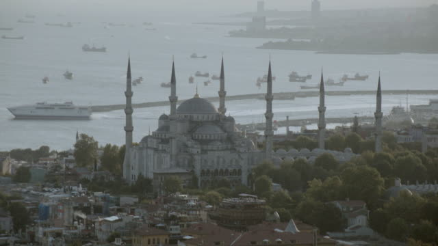 AERIAL The Sultan Ahmed Mosque overlooking the Bosphorus Strait crowded with boats and ships / Istanbul, Turkey