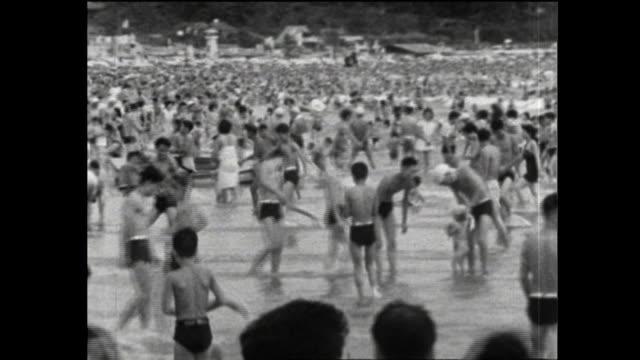 the summer of 1953 beach packed with seagoers - 水着点の映像素材/bロール