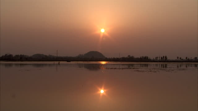 the sun at golden hour casts a reflection on the surface of a lake. - tay ninh stock videos & royalty-free footage