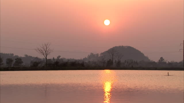 the sun at golden hour reflects on the surface of a lake. - tay ninh stock videos & royalty-free footage
